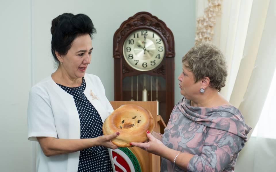 Дилбар Асланова передает узбекскую лепешку Эльвире Садыковой