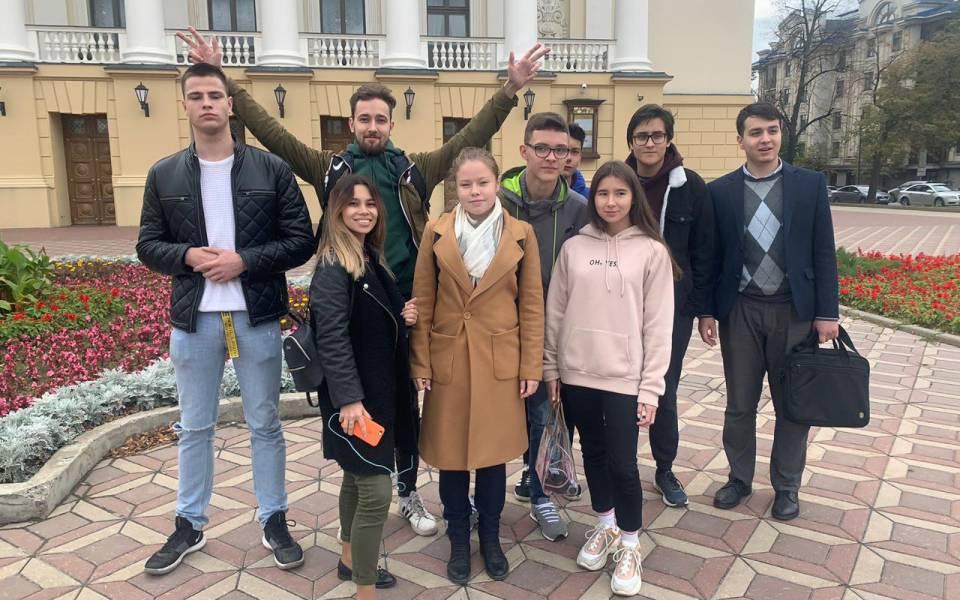Команда молодых людей позируют около исторического здания Казани